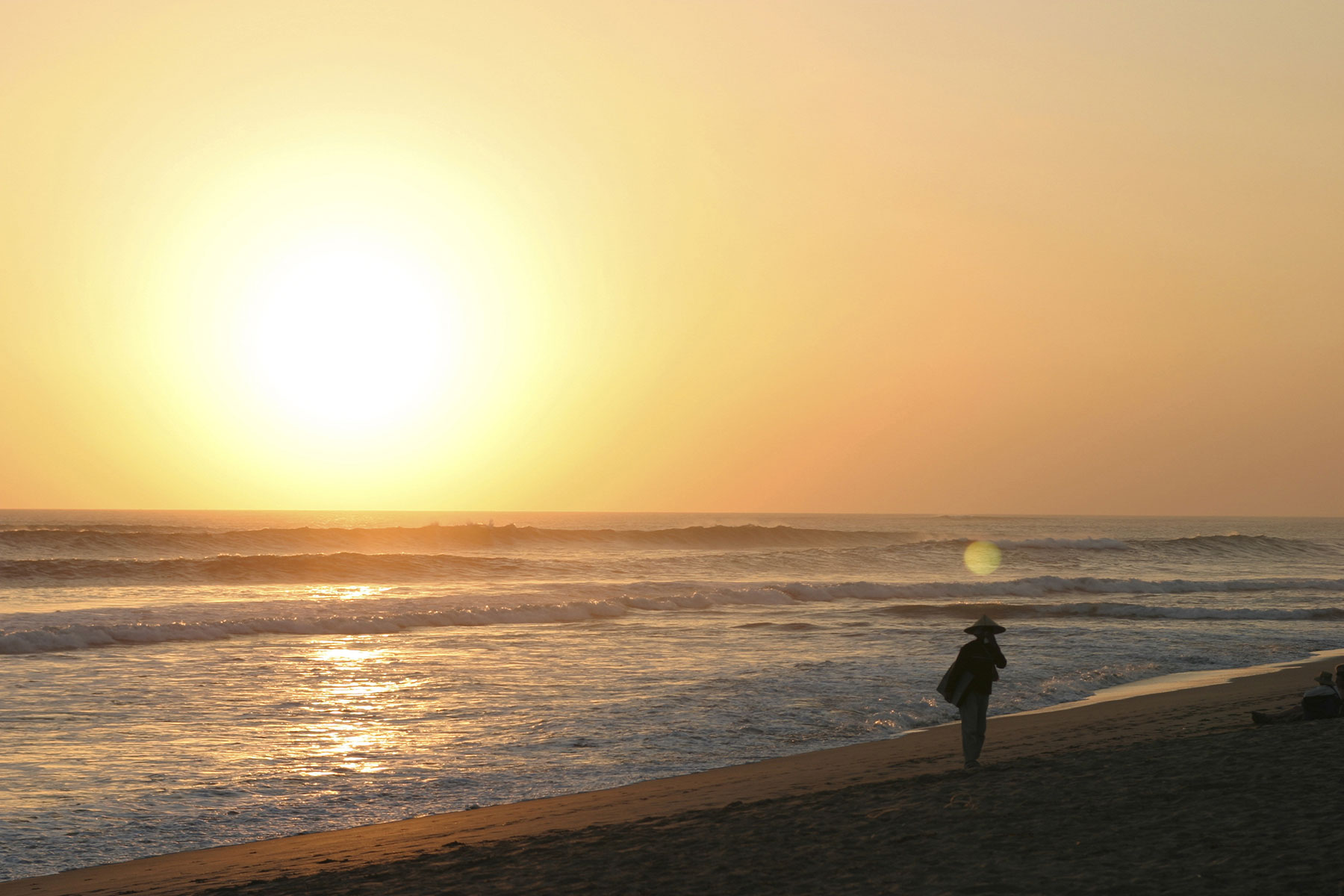 Man walking on empty beach at sunset in Indonesia