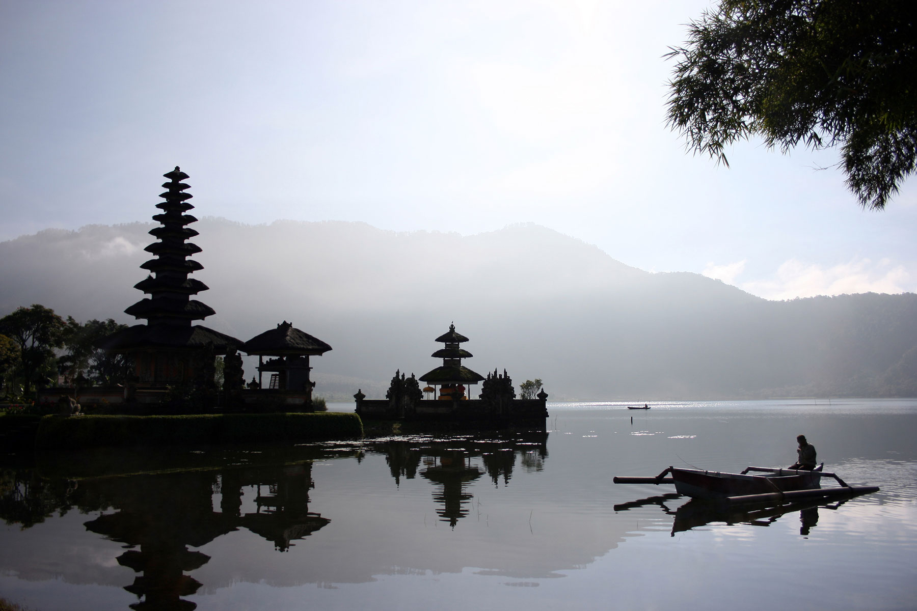 Fisherman in boat early morning with temple in the background